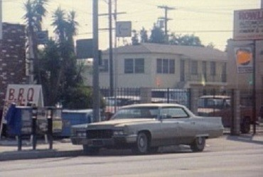 A cadillac de ville is parked on the side of a street next to a sign for BBQ