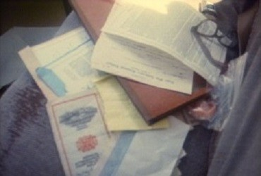 Several important documents are laid out on the back seat of a car