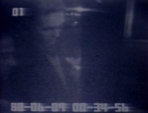 Black and white screenshot of security footage, two man stand infront of an atm.