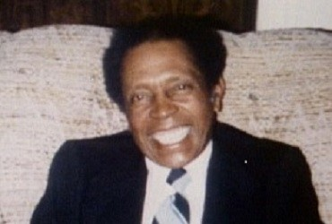 Rogest Cain smiling at the camera, sitting on a couch in a dark blue suit