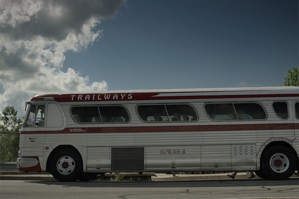 Bus parked outside with clouds
