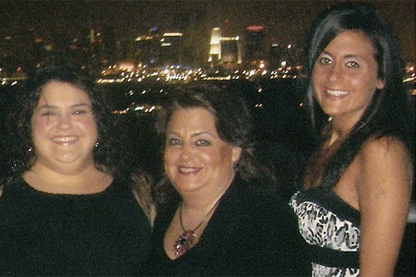 Mother and two daughters with city lights behind them