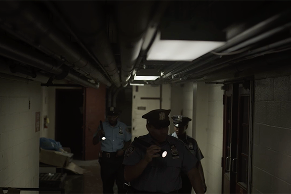 Three police officers with flashlights in a basement hallway