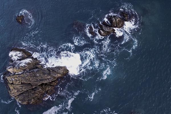 waves crash into rocks