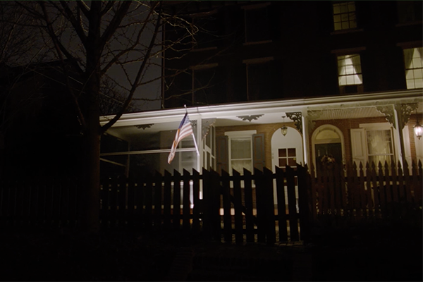 House with flag and fence at night