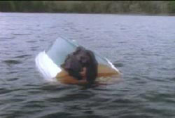 An overturned boat in the middle of a lake.