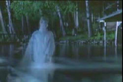 A translucent female in a white robe coming out of water.