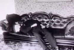 A corpse laying on an ornate black leather couch.