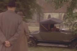 Two men in hats and trenchcoats walking towards a car abandoned on a residential street.