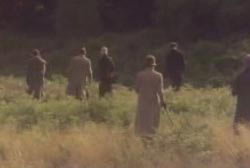 roup of men in hats and trenchcoats searching through a field.
