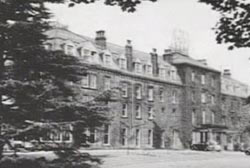 A black and white photo of a large 4 story building, an old fashioned spa.