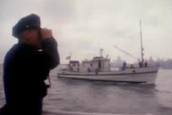 A police officer searches the water through binoculars, there is a coast guard boat in the background.