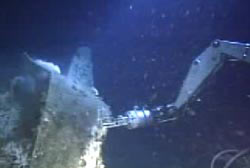 A mechnical arm of a submarine touches a submerged navy bomber.