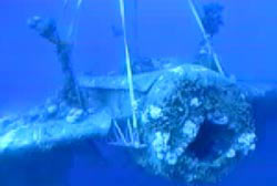 A crane lifts a submerged navy bomber through the water.