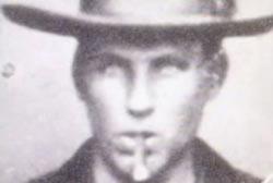 Headshot of Brushy Bill, age 17, wearing a hat and smoking a cigar.