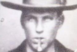Headshot of Brushy Bill, age 17, wearing a hat and smoking a cigar.