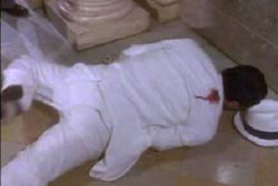 A man in a white suit is laying face down on the ground, he is bleeding from a gun shot wound in his right shoulder.