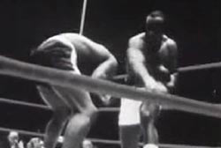 Sonny Liston is in a boxing ring, he is fighting Floyd Patterson who is double over after being punched in the face.