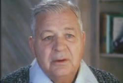 An old white man in a collared shirt and sweater.