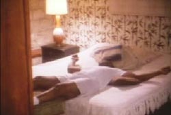 Sonny Liston is sprawled on a bed, he is wearing a white t-shirt, boxers and socks. There is a lamp on the bedside table.