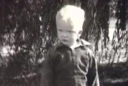 A small boy with blonde hair is standing wearing a jumpsuit.
