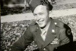 A smiling soldier in uniform, his curl hair tucked into his hat.