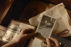 A woman holding a photo of her brother over other old family photos.