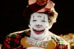 A clown in white makeup, a red flannel suit and a bowtow that says 'Curly'