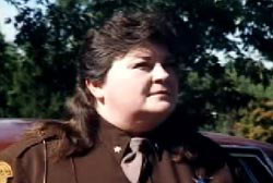 A woman with a brunette mullet, wearing a sheriff's deputy uniform.