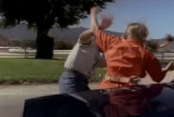 A woman in an orange jumpsuit is attacking another person next to a car.