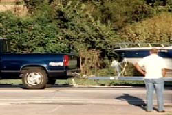 A man in a white tshirt and jeans stands in front of a blue pick up truck towing a boat.