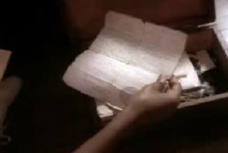 A hand takes an old letter from a box.
