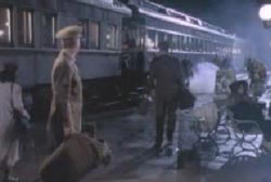 Two uniformed soldiers are on a train platform. One is walking away while the other is watching him.