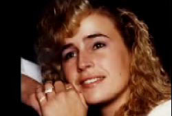 A young woman is posing, reasting her heads on her hands,  her blonde hair is curly and she is wearing a white shirt.