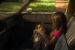 A young girl seats in the passenger seat of a station wagon, holding a toy.