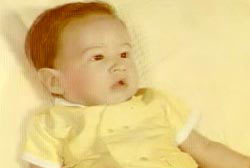 A baby in a yellow outfit on a yellow bed.