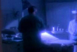 An autopsy room with a man in shadow standing over a corpse on a gurney.