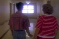 Two people walking down a white hallway, they are wearing red striped shirts.