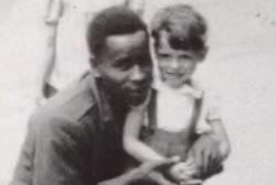 An african american man kneeling next to a small caucasian child.