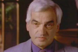 An elderly caucasian man with grey hair wearing a purple suit.