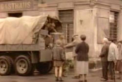 Several people are standing around a military truck as supplies are distributed during WWII.