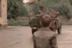A small caucasian boy is watching as soldiers drives away in a jeep.