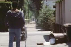 A man in a hoodie is standing with a grocery cart in an alley, there is trash can knocked over.