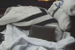 A white sweater and a wallet are on a car seat.