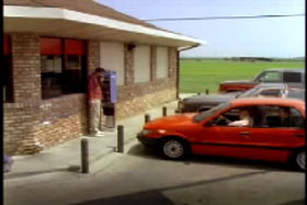 A red sedan parked next to a brick and mortar store. There is a man on a red shirt on a payphone.