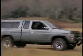 A gray pick up truck driving fast