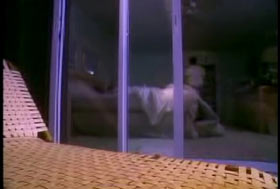 A beach chair infront of a hotel room, a man can be seen through the sliding glass doors.