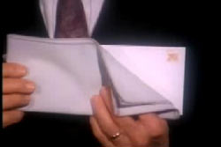A man in a suit holding an envelope.