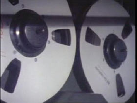 A vintage recorder, the two large reels of tape spinning.