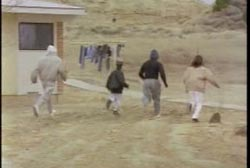 Four local men walking by a house, searching.